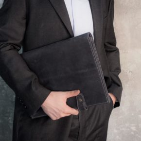 man holding leather folder