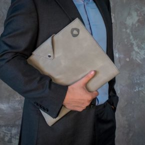 man holding grey leather padfolio