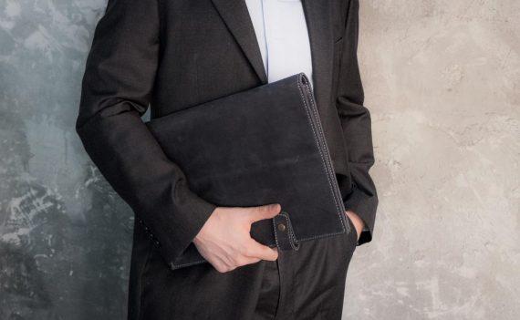 man holding leather folder